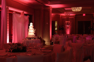 Elegant wedding uplighting in a hotel ballroom with a contrasting cake spot