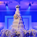 A grand and elegant wedding cake with lit cake spot in a Colorado hotel ballroom for this bride's wedding