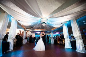 Wedding up lighting in a vibrant color with ceiling fabric treatment