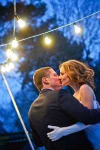 Romantic Colorado mountain wedding with the Bride kissing the Groom under our special bistro lights