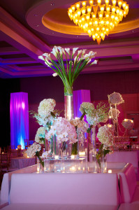 Hotel wedding with lit floral centerpieces and elegant wedding lighting